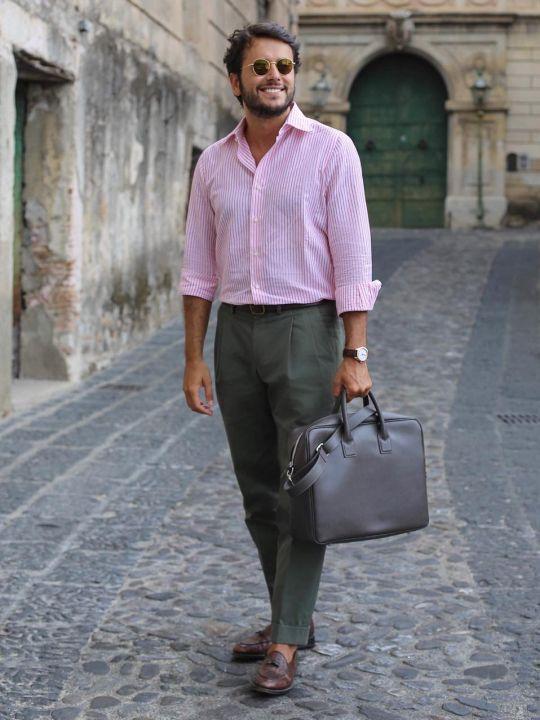 Vyras vilki rožinius marškinius,tamsiai žalias kelnes, avi rudus batus