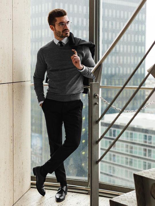 Vyras vilki pilką megztinį, baltus marškinius, juodas kelnes