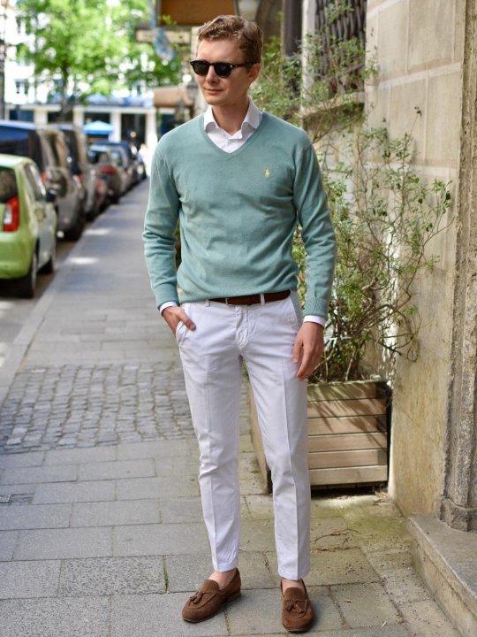 Vyras vilki žalią megztinį, baltus marškinius, baltas kelnes