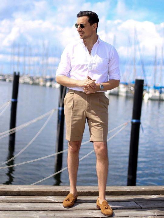 Vyras vilki baltus marškinius, šviesiai rudus šortus, avi rudus batus