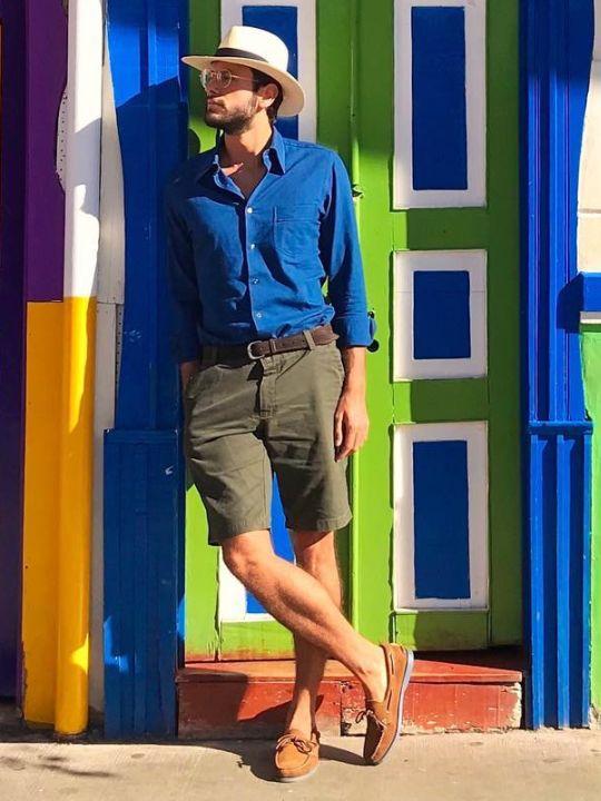 Vyras vilki mėlynus marškinius, žalius šortus, avi rudus batus