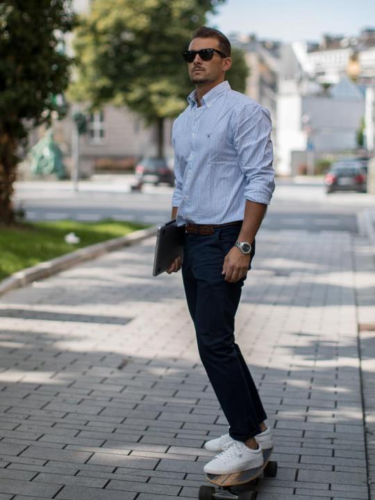 Vyras vilki šviesiai mėlynus marškinius, tamsiai mėlynas kelnes, avi baltus sportinius batelius