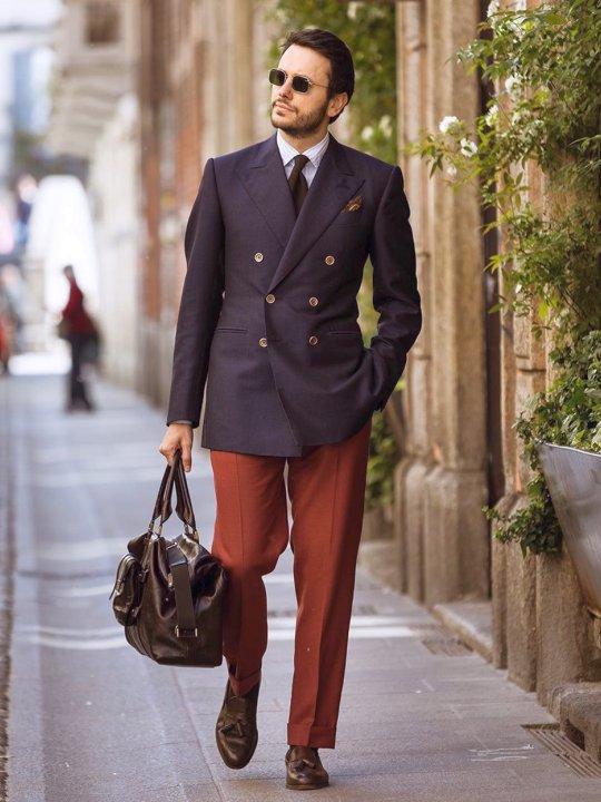 Vyras vilki tamsiai mėlyną švarką ir raudonas kelnes