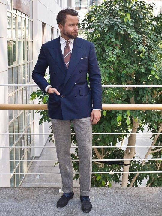 Vyras vilki mėlyną švarką ir pilkas kostiumines kelnes