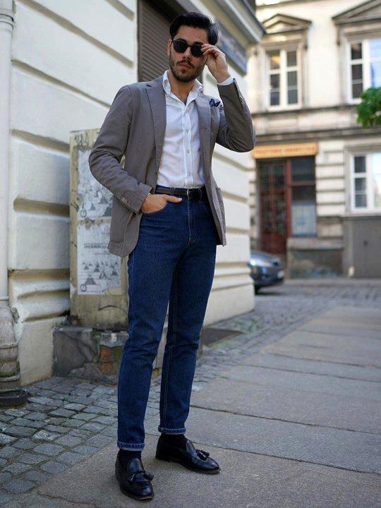 Vyras vilki pilką švarką ir mėlynus džinsus