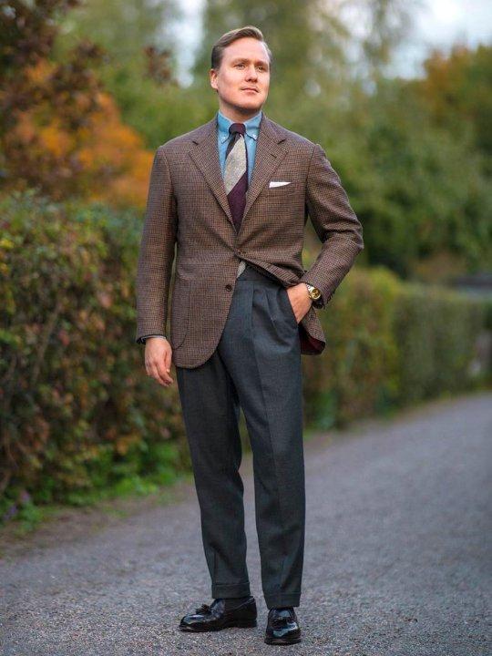 Vyras vilki rudą švarką ir pilkas kostiumines kelnes