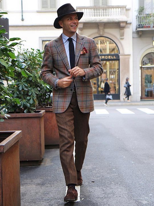 Vyras vilki šviesiai rudą švarką ir rudas kelnes