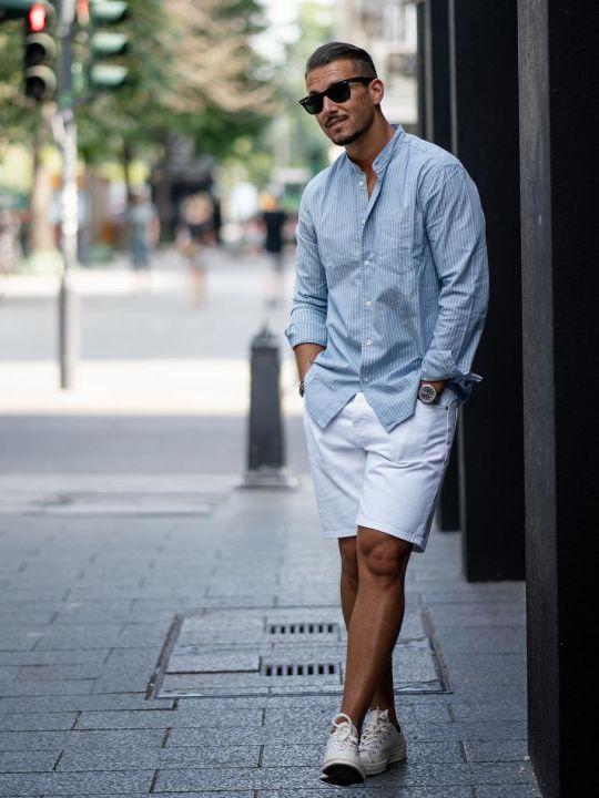 Vyras vilki šviesiai mėlynus marškinius, baltus šortus, avi baltus sportinius batelius