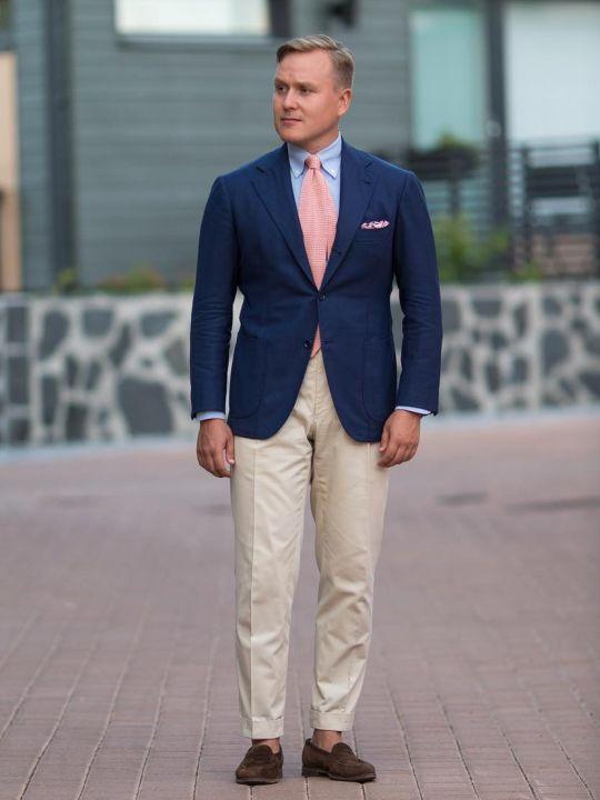 Vyras vilki mėlyną švarką, šviesiai mėlynus marškinius, šviesias kelnes, avi rudus batus