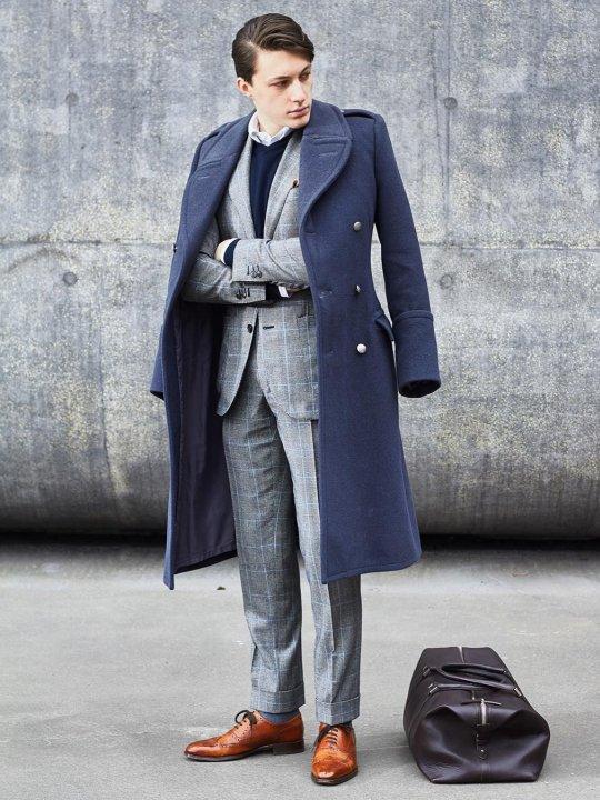 Vyras vilki mėlyną paltą ir pilką kostiumą