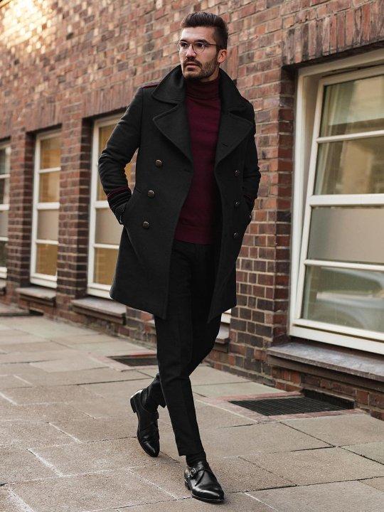Vyras vilki juoda paltą ir juodas kelnes