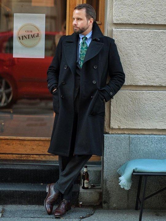 Vyras vilki tamsiai mėlyną paltą ir pilkas kelnes