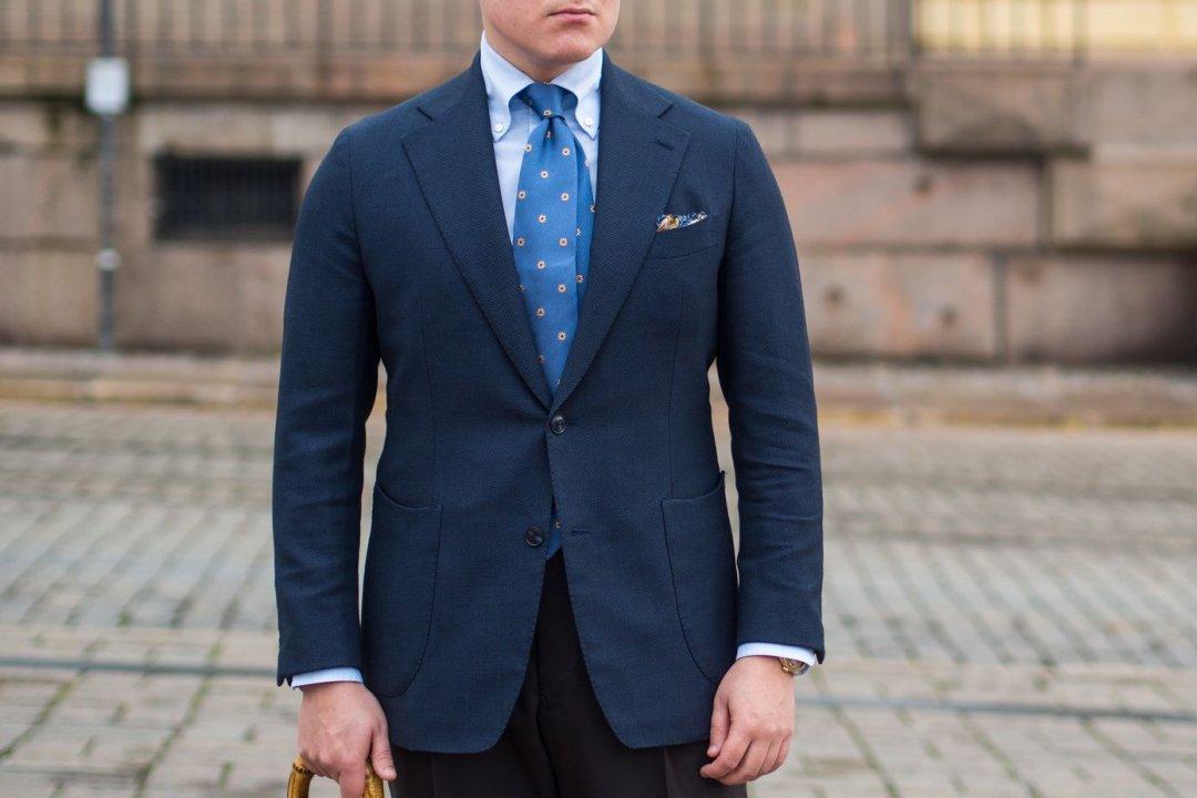 Vyras vilki vienaeilį dviejų sagų mėlyną švarką
