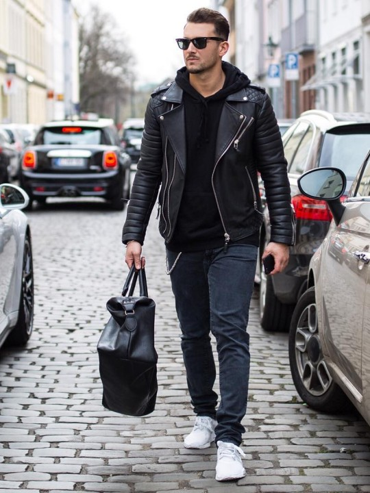 Vyras vilki juodą biker striukę, juodą džemperį su gobtuvu, pilkus džinsus