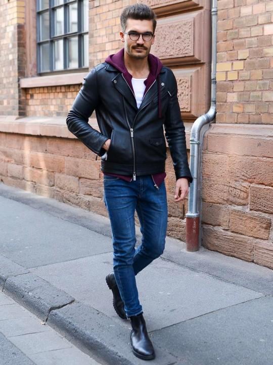Vyras vilki juodą biker striukę, tamsiai raudoną džemperį su gobtuvu, mėlynus džinsus