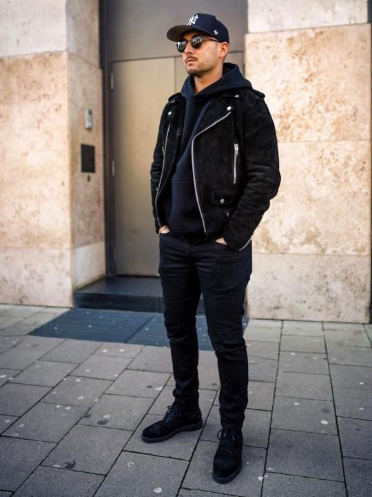 Vyras vilki juodą biker striukę, juodą džemperį su gobtuvu, juodus džinsus