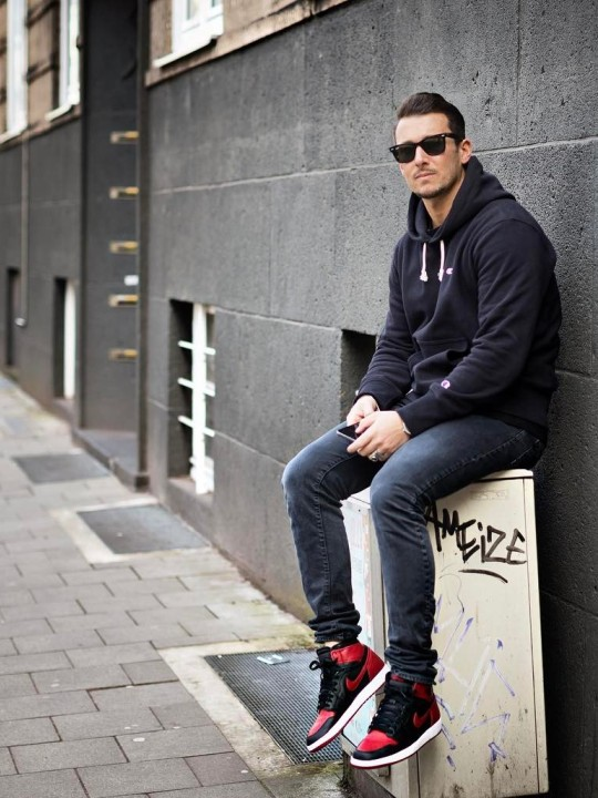 Vyras vilki juodą džemperį su gobtuvu, tamsiai pilkus džinsus