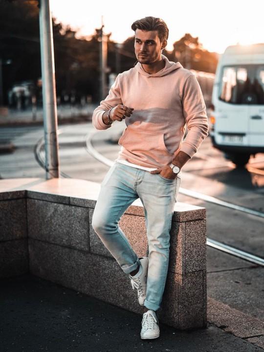 Vyras vilki rožinį džemperį su gobtuvu, šviesiai mėlynus džinsus