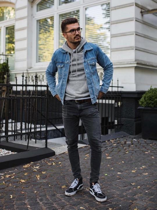 Vyras vilki mėlyną džinsinį švarką, pilką džemperį su gobtuvu, tamsiai pilkus džinsus