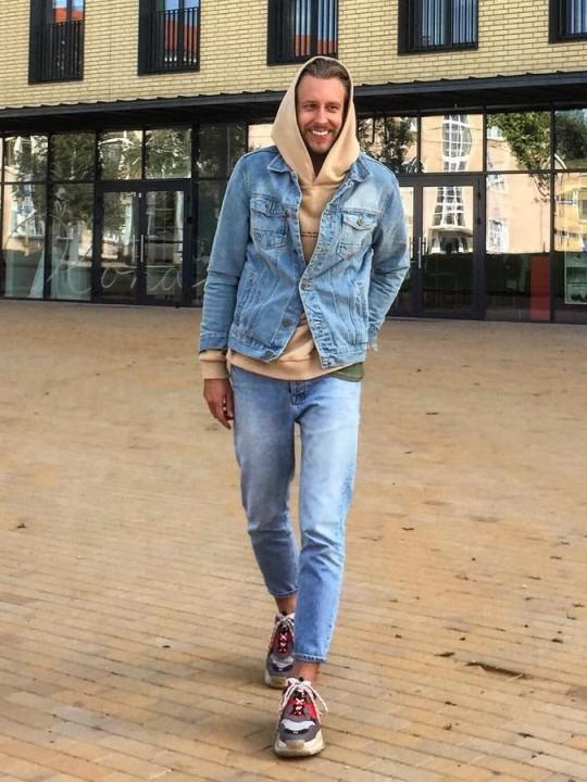 Vyras vilki mėlyną džinsinį švarką, šviesiai rudą džemperį su gobtuvu, mėlynus džinsus