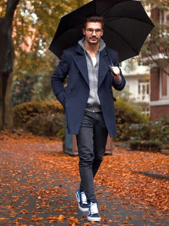 Vyras vilki tamsiai mėlyną paltą, pilką džemperį su gobtuvu, tamsiai pilkus džinsus