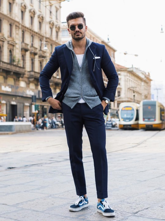 Vyras vilki mėlyną kostiumą, pilką džemperį su gobtuvu