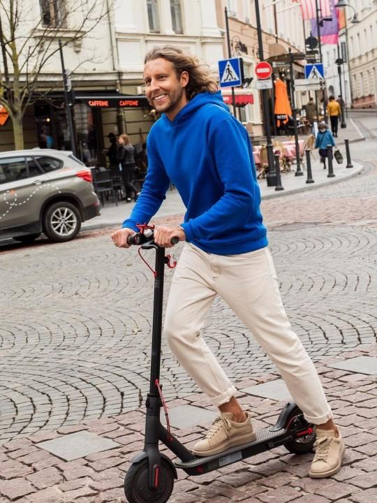 Vyras vilki mėlyną džemperį su gobtuvu, baltas sportines kelnes