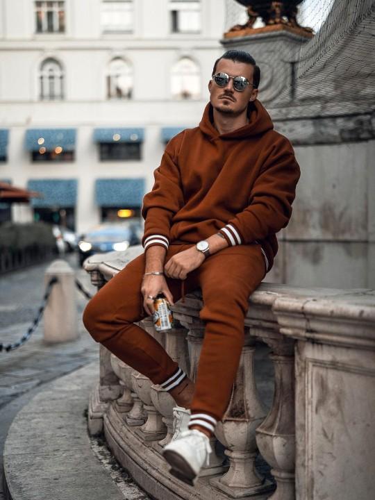 Vyras vilki rudą džemperį su gobtuvu, rudas sportines kelnes