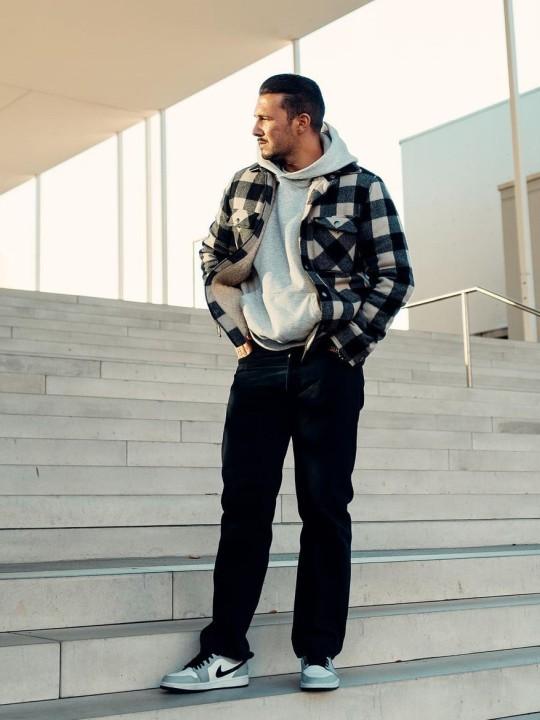 Vyras vilki šviesiai pilką džemperį su gobtuvu, juodas sportines kelnes