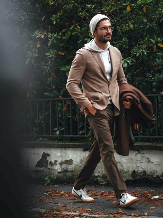Vyras vilki rudą švarką, baltą džemperį su gobtuvu, tamsiai rudas kelnes