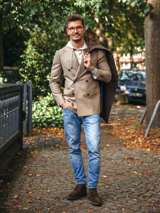 Vyras vilki rudą švarką, šviesiai rudą džemperį su gobtuvu, mėlynus džinsus