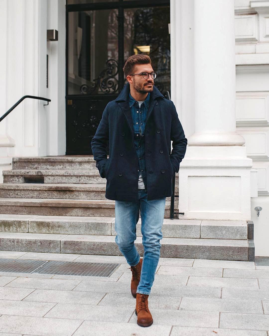 Vyras vilki tamsiai mėlyną paltą, mėlynus marškinius, šviesiai mėlynus džinsus