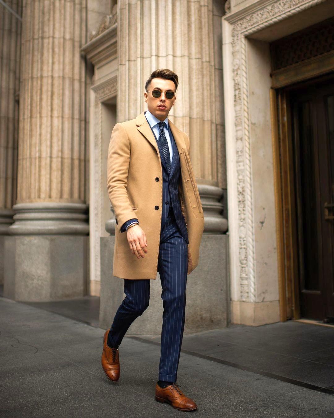 Vyras vilki camel paltą, mėlyną kostiumą