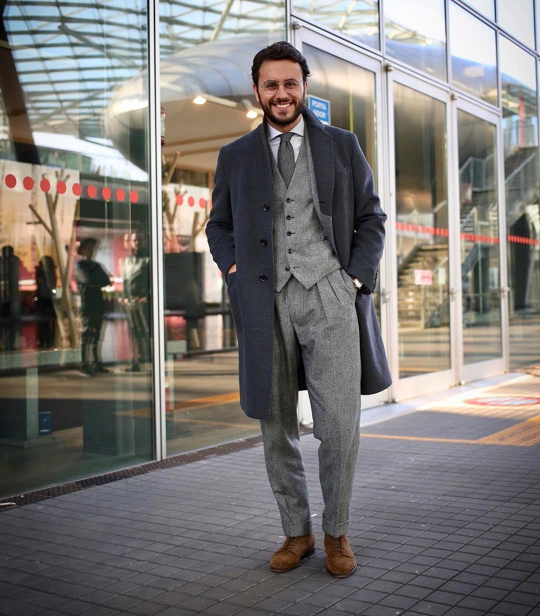 Vyras vilki mėlyną paltą, pilką kostiumą