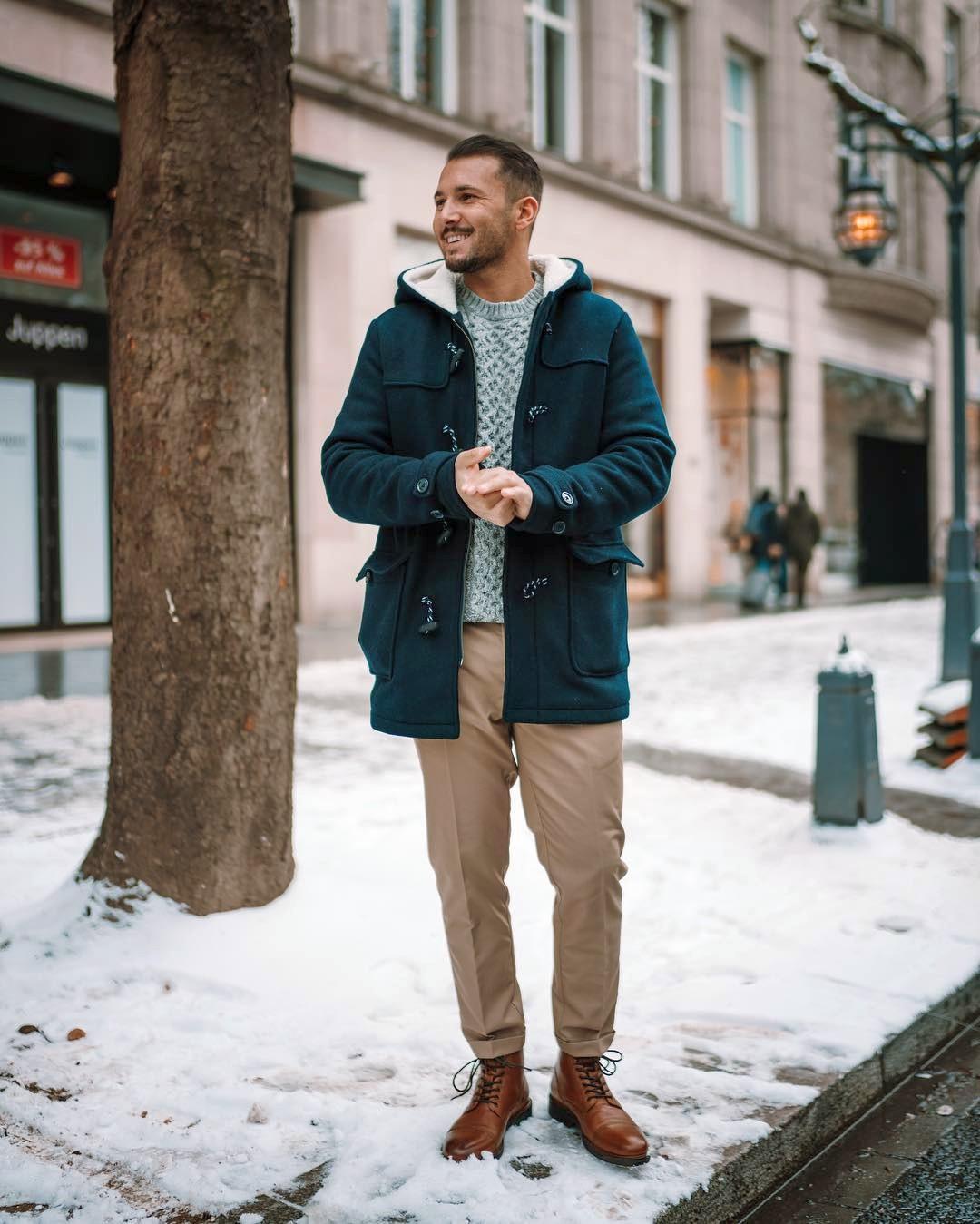 Vyras vilki mėlyną žieminę striukę, šviesiai pilką megztinį, šviesiai rudas kelnes