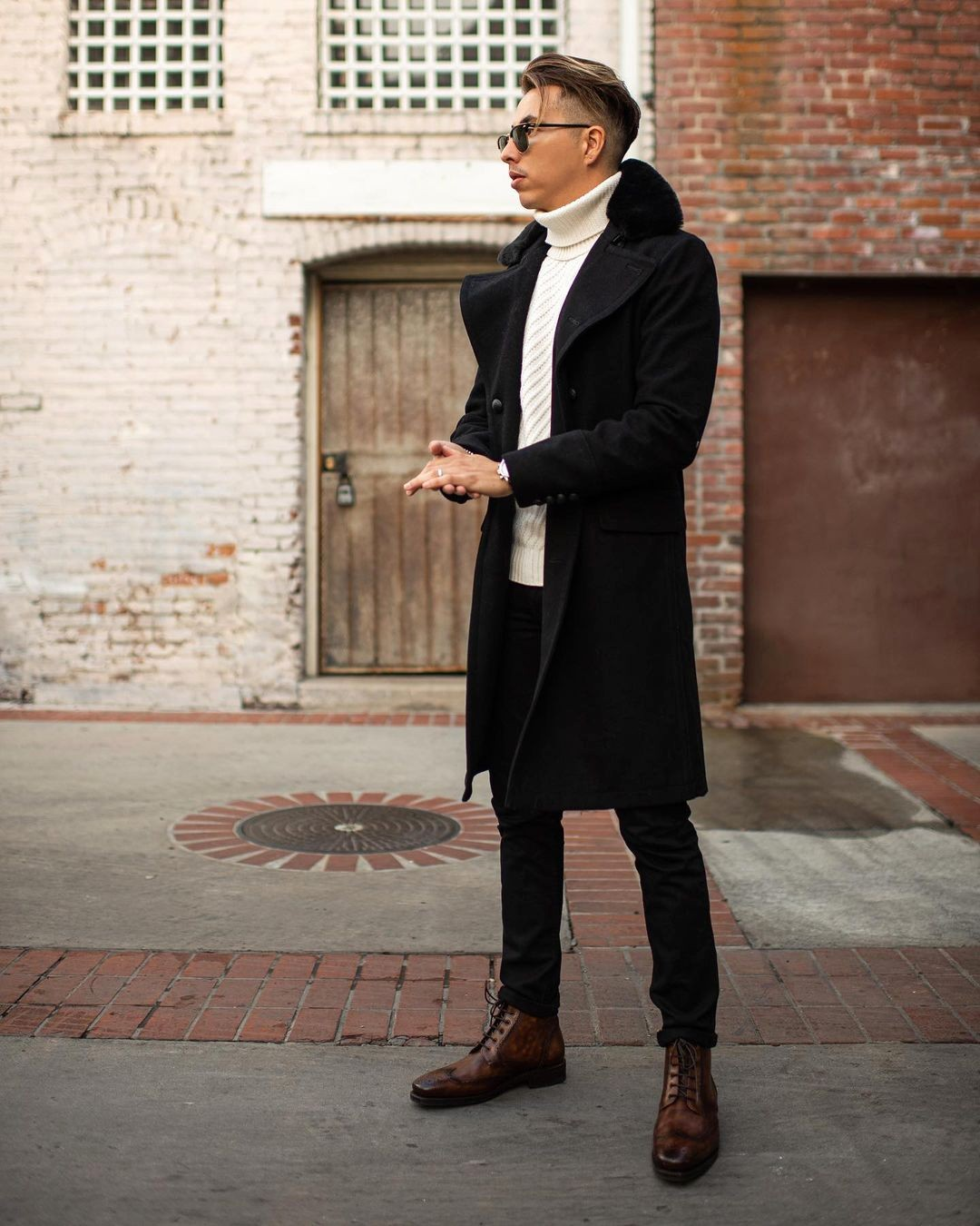 Vyras vilki juodą paltą, baltą megztinį, juodus džinsus