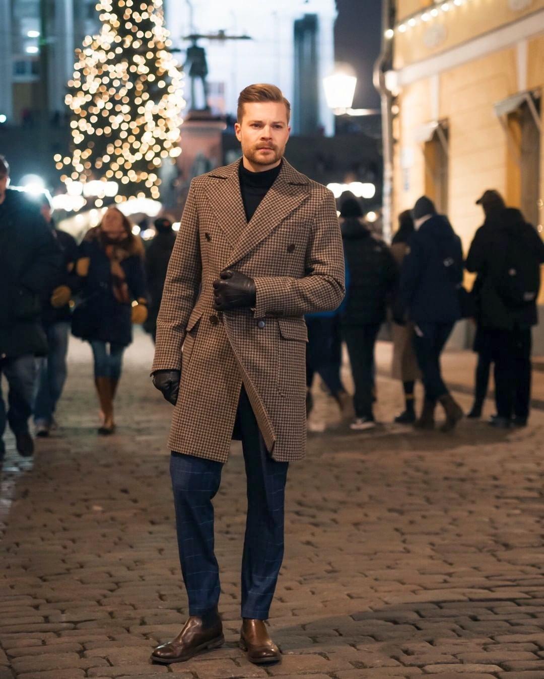 Vyras vilki rudą paltą, tamsiai mėlybą megztinį, mėlynas kelnes