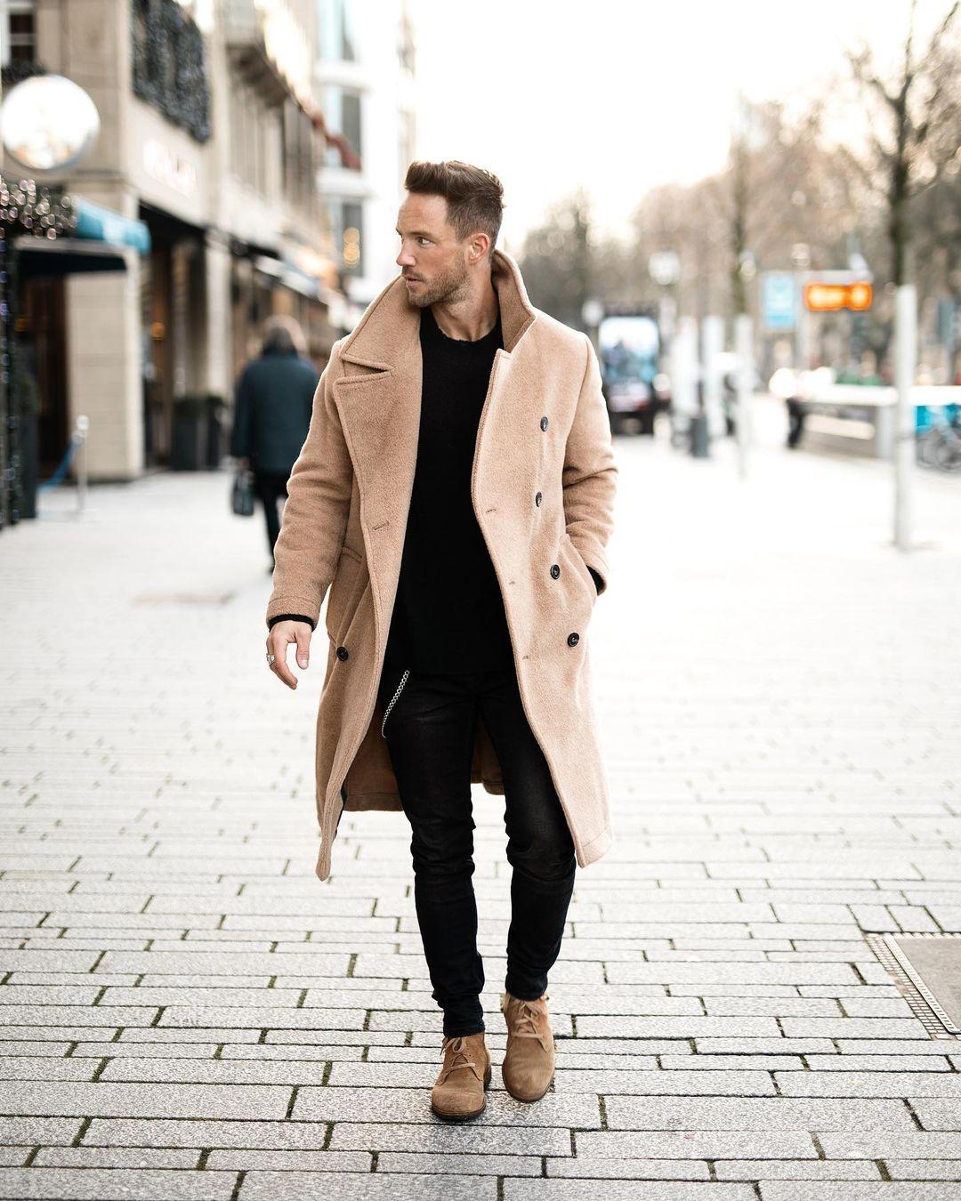 Vyras vilki camel paltą, juodą megztinį ir džinsus