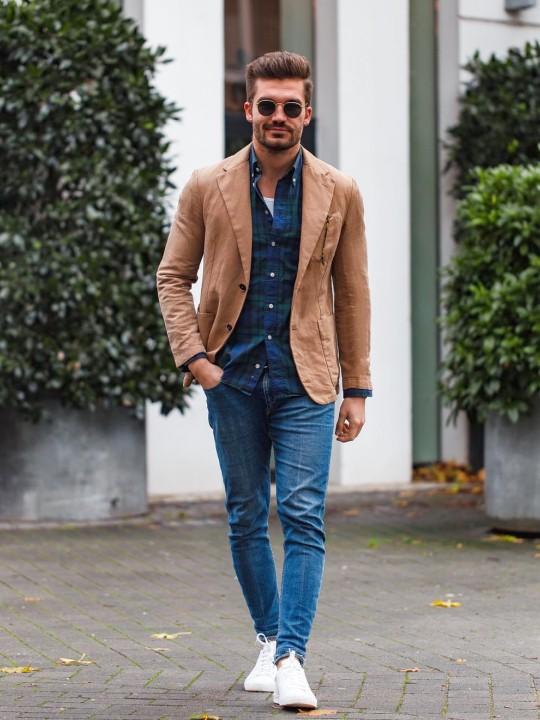 Vyras vilki camel švarką ir mėlynus džinsus