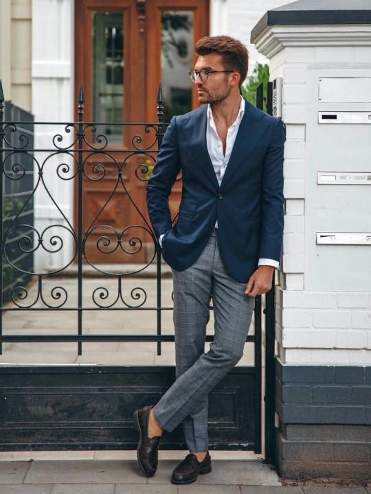 Vyras vilki mėlyną švarką ir pilkas kelnes