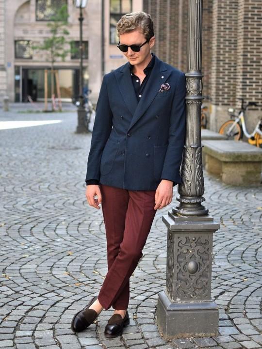 Vyras vilki mėlyną švarką ir raudonas kelnes