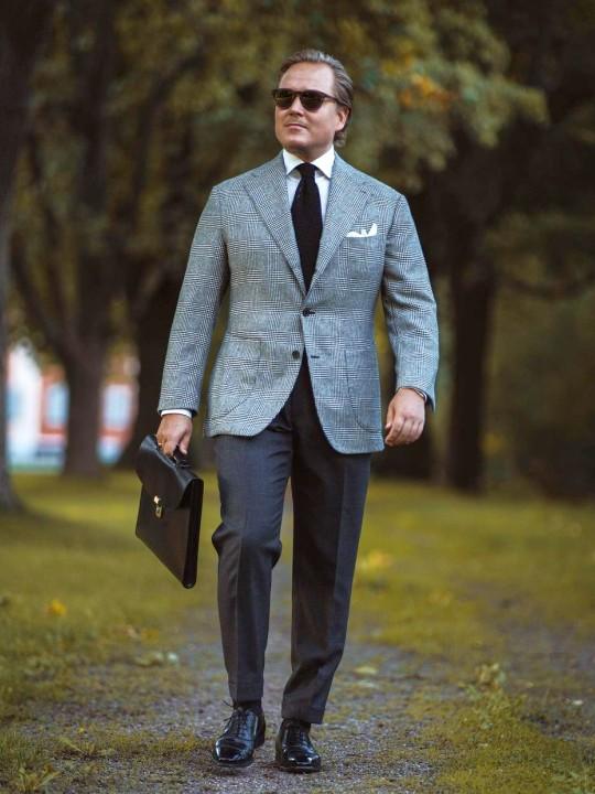 Vyras vilki šviesiai pilką švarką ir tamsiai pilkas kelnes