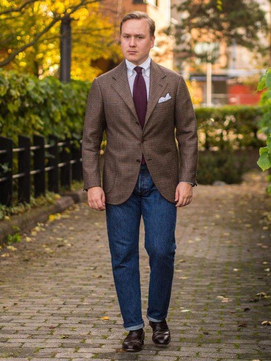 Vyras vilki rudą švarką ir mėlynus džinsus