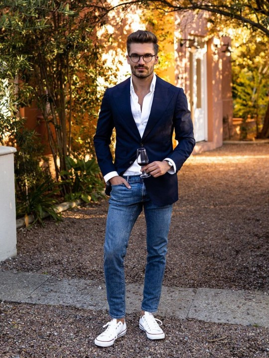 Vyras vilki tamsiai mėlyną švarką ir mėlynus džinsus