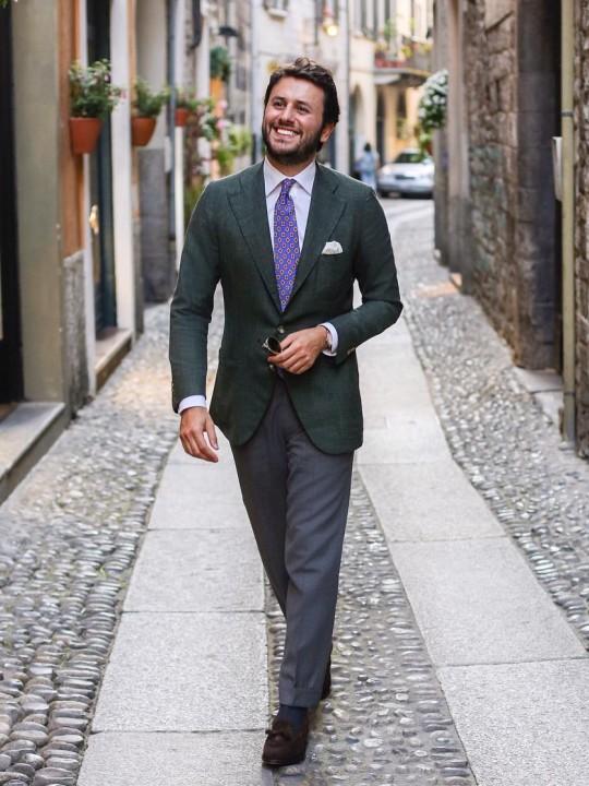 Vyras vilki tamsiai žalią švarką ir pilkas kelnes