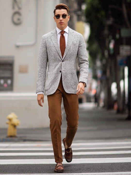 Vyras vilki pilką švarką, rudas kelnes, avi rudus batus