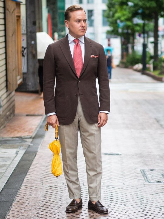 Vyras vilki rudą švarką, baltus marškinius, pilkas kelnes, avi rudus batus