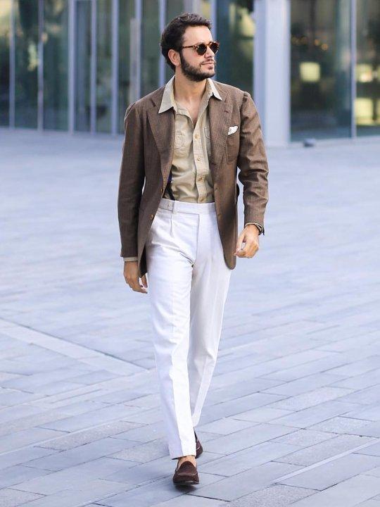 Vyras vilki rudą švarką, baltas kelnes, avi rudu batus