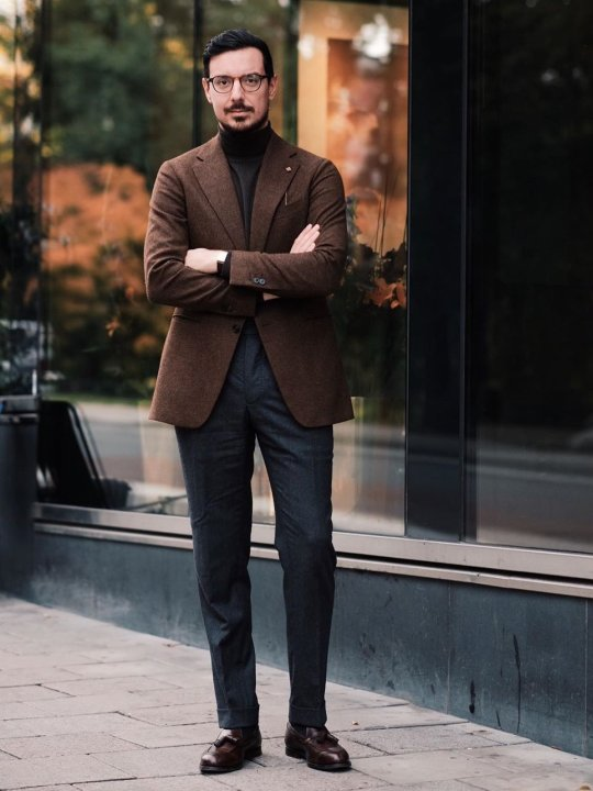 Vyras vilki rudą švarką, tamsiai rudą megztinį, pilkas kelnes, avi rudus batus