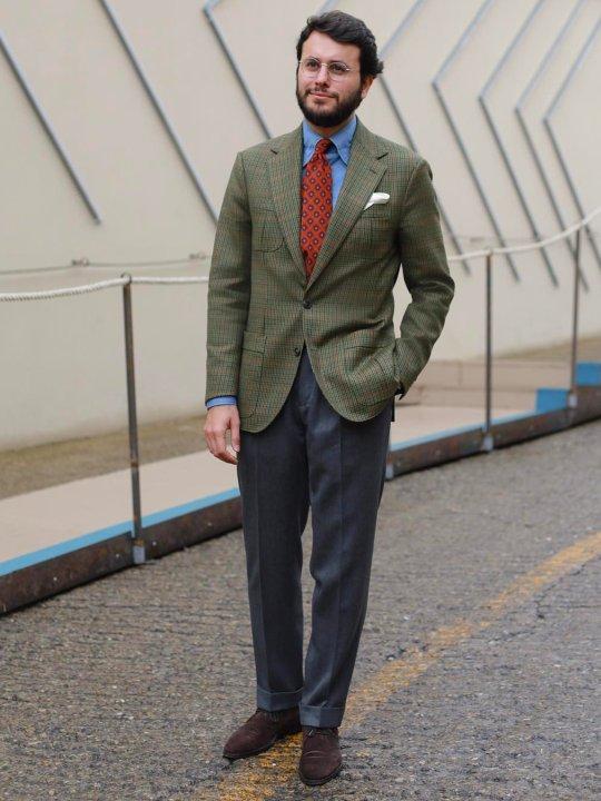 Vyras vilki žalią švarką, pilkas kelnes, avi rudus batus